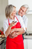 Senior couple in kitchen with wine Stock Photography
