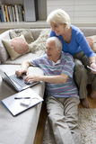 Senior couple with laptop computer in sitting room Royalty Free Stock Images