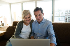 Senior couple with laptop sitting on a couch in living room Royalty Free Stock Photography
