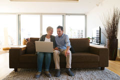 Senior couple with laptop sitting on a couch in living room Royalty Free Stock Image
