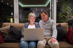 Senior couple with laptop sitting on a couch in living room Royalty Free Stock Images