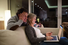 Senior couple with laptop sitting on couch shopping online Royalty Free Stock Image