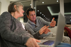 Senior couple with laptop and smartphone sitting on couch Royalty Free Stock Image