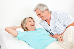 Senior couple laughing in bed Stock Photography