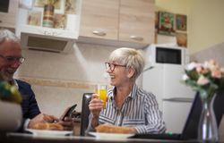 Senior couple laughing in kitchen stock photography