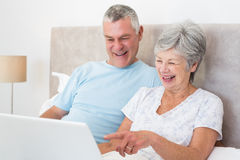 Senior couple laughing while using laptop in bed Stock Photo