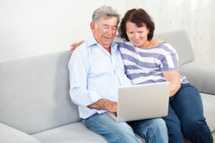 Senior couple laughing while using laptop Stock Images