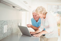 Senior couple laughing while using laptop in kitchen Royalty Free Stock Images
