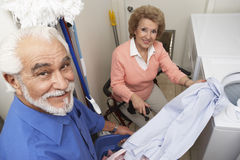 Senior Couple With Laundry By Washing Machine Stock Image