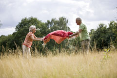 A senior couple laying a picnic blanket on the grass Royalty Free Stock Photo