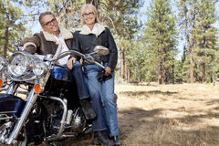 Senior couple lean on motorcycle in forest Stock Images