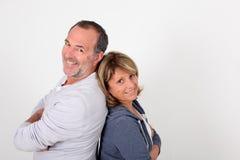 Senior couple leaning backs on eachother isolated. Senior couple standing back to back on white background royalty free stock images