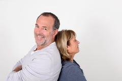 Senior couple leaning backs on eachother. Senior couple standing back to back on white background royalty free stock image