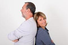 Senior couple leaning backs on eachother. Senior couple standing back to back on white background stock photo
