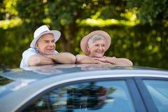 Senior couple leaning on car roof Stock Photo