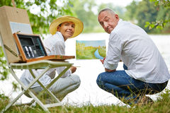 Senior couple learning painting in nature in summer Royalty Free Stock Photo