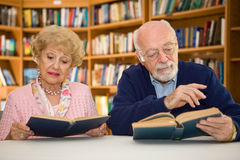 Senior Couple at the Library. Senior couple together reading at the library Royalty Free Stock Images