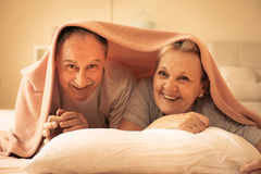 Senior couple lie together under the covers. stock images