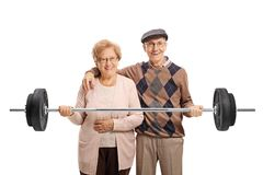 Senior couple lifting a barbell together stock photo