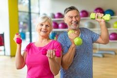 Senior couple lifting dumbbells stock image