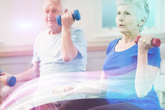 Senior couple lifting dumbbells. While sitting at gym Royalty Free Stock Photography