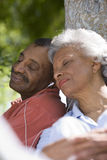 Senior couple listening to MP3 player in garden, sharing earbud headphones, leaning against tree trunk, eyes closed, close-up Stock Photography