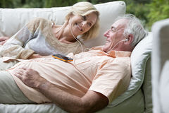 Senior couple listening to music on shared headphones on outdoor sofa Stock Image