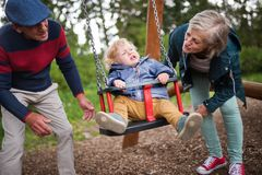 Senior couple with little boy at the playground. Royalty Free Stock Images