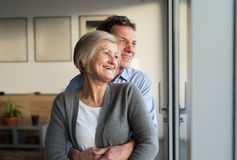 Senior couple in living room standing at the window, hugging Stock Photos