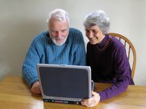 Senior couple look at laptop. A senior couple looks at a laptop computer screen together Royalty Free Stock Image