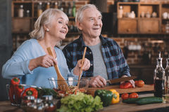 Senior couple looking away while cooking together Royalty Free Stock Image