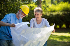 Senior couple looking at blueprint in the garden. On a sunny day Stock Image
