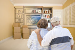 Senior Couple Looking At Drawing of Entertainment Unit In Room. Senior Couple In Room With Moving Boxes Looking At Drawing of Entertainment Unit Royalty Free Stock Photo