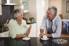 Senior couple looking at each other while having coffee at home Royalty Free Stock Photography