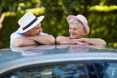 Senior couple looking at each other while leaning on car roof Royalty Free Stock Photos