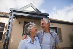 Senior couple looking at each other while standing against house. Smiling senior couple looking at each other while standing together against house Royalty Free Stock Photos