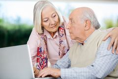 Senior Couple Looking At Each Other While Using Stock Photo