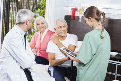 Senior Couple Looking At Female Nurse While Sitting By Doctor Stock Photo