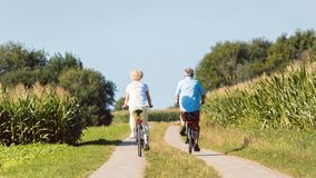 Senior couple looking forward with confidence while riding bicycles. Full length of a senior active couple smiling and looking forward with confidence and stock photo