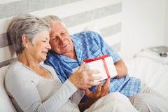 Senior couple looking at gift box Royalty Free Stock Image