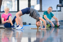 Senior couple looking at girl doing bridge exercise in fitness class Stock Photo