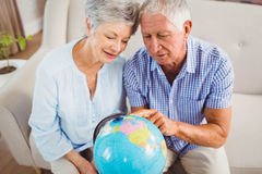 Senior couple looking at a globe Royalty Free Stock Image