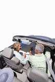 Senior couple looking at map in convertible car, cut out Royalty Free Stock Photo