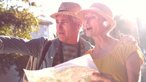 Senior couple looking at the map and pointing stock video footage