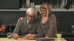 Senior couple looking old photo album. And smiling stock video footage