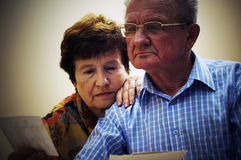 Senior couple looking at old photographs. Reminisce about the past royalty free stock image