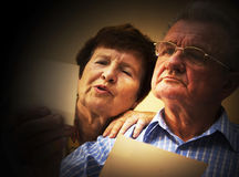 Senior couple looking at old photographs. royalty free stock images