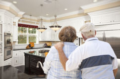 Senior Couple Looking Over Beautiful Custom Kitchen Stock Photo