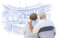 Senior Couple Looking Over Blue Custom Kitchen Design Drawing Stock Photo