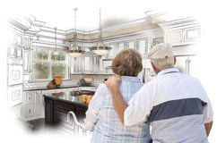 Senior Couple Looking Over Custom Kitchen Design Drawing and Pho Royalty Free Stock Photos